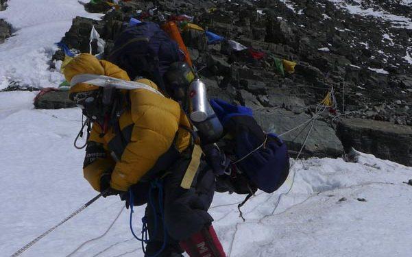 Un sherpa en la cara norte del Everest desciende muy cargado (2013).  (Carla Pérez/Esteban Mena/ Somos Ecuador)