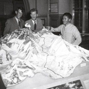 Edmund Hillary, John Hunt y Tensing Norway ante una maqueta del Everest con el glaciar de Khumbu