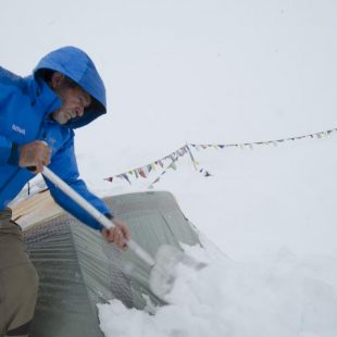 Carlos Soria limpia con la pala la nieve caída sobre su tienda  ((c) Darío Rodríguez/Desnivel)
