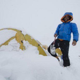 El médico Carlos Martínez sonrie mientras limpia de nieve su tienda  ((c) Darío Rodríguez/Desnivel)