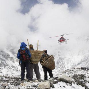 Un helicóptero despega del campo base del Everest (2011) ante la mirada de un grupo de porteadores.  (Darío Rodríguez/DESNIVEL)