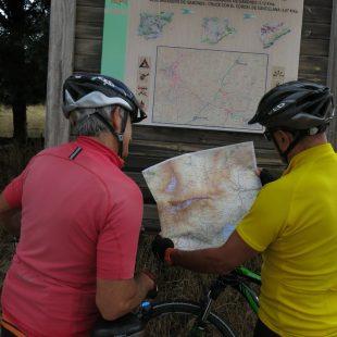 Dos cicloturistas consultan un mapa junto a un panel de la Cañada Real Soriana Occidental
