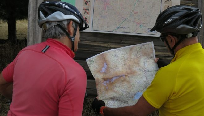 Dos cicloturistas consultan un mapa junto a un panel de la Cañada Real Soriana Occidental