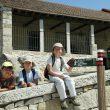 Jóvenes senderistas sentados frente a la iglesia de El Berrueco con un poste de dirección de la Senda del Genaro. GR 300  (Víctor Guerra)