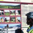 Un excursionista consulta un panel del mismo camino que explica las caracterísitcas particulares del valle de Cintora