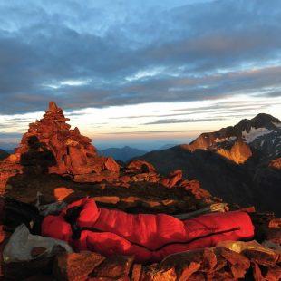 La roca rojiza de la cumbre del Forca-Clarabides parece arder con las primeras luces del día.